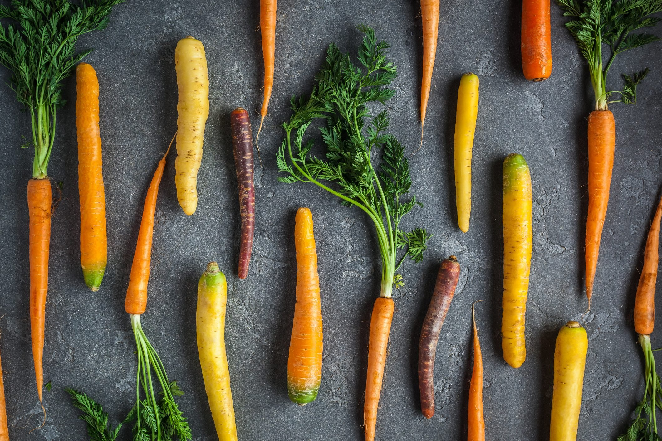 Fresh colorful carrots on dark background. Flat lay, top view