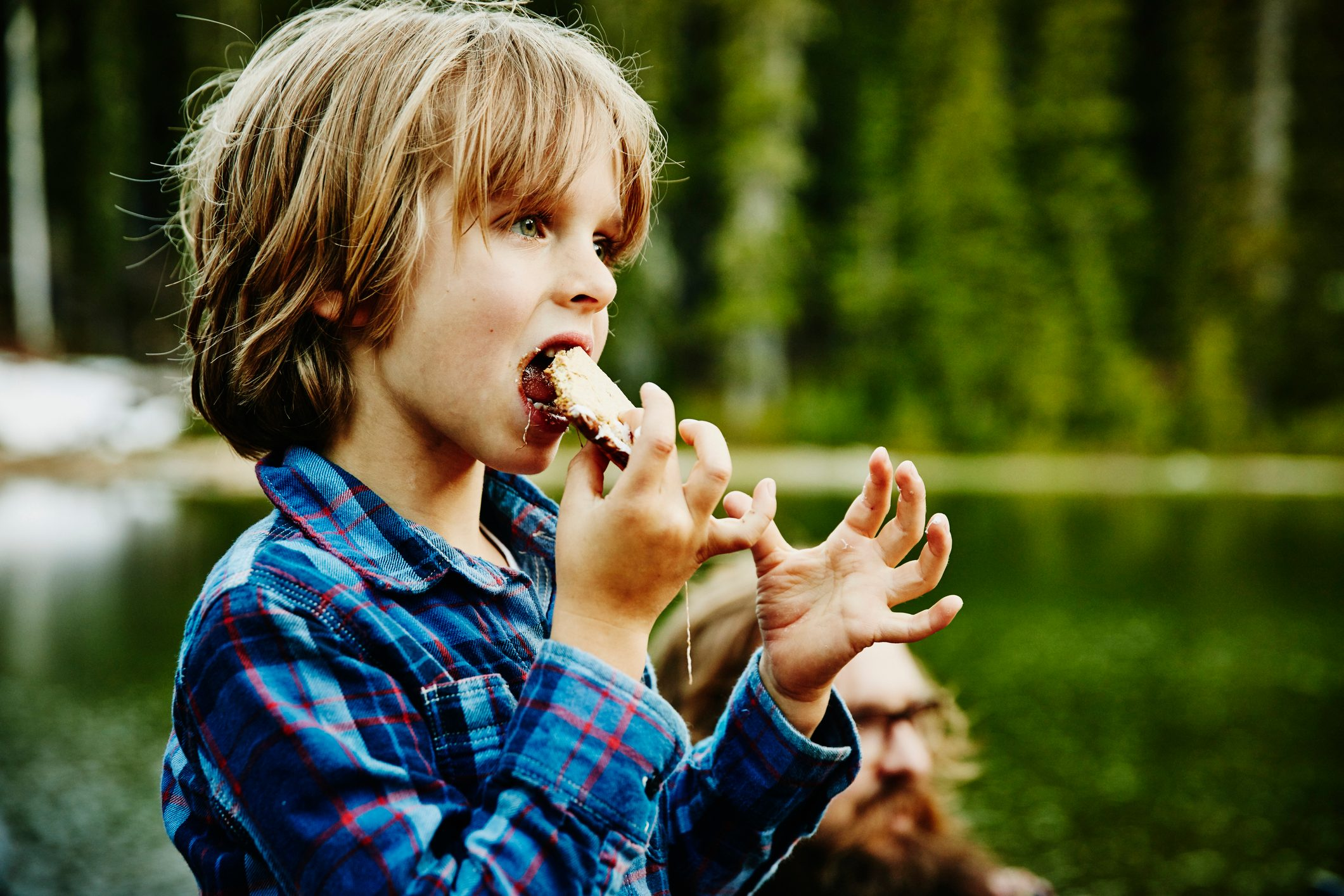 Young boy eating smore while camping with family