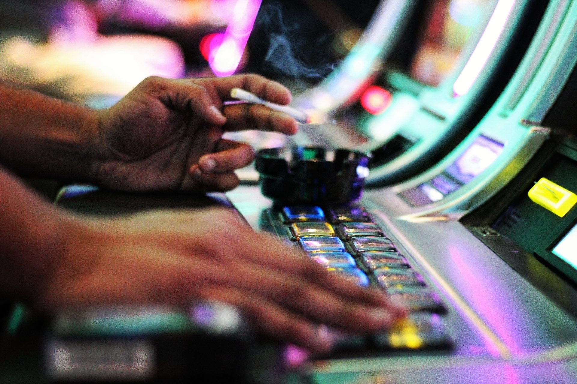 Close-Up Of Hands Playing Slot Machine