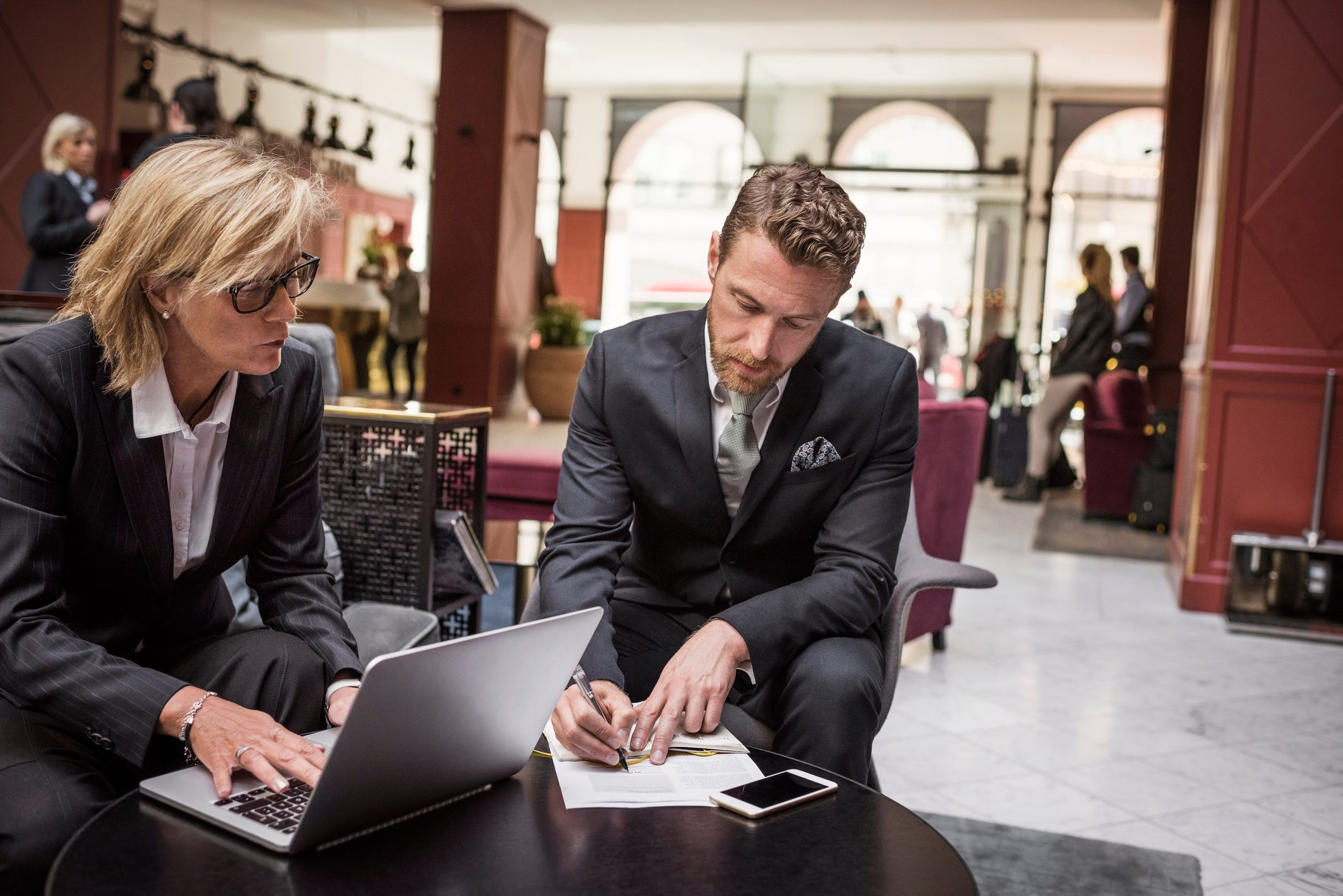 Businesswoman looking at partner signing agreement in hotel reception