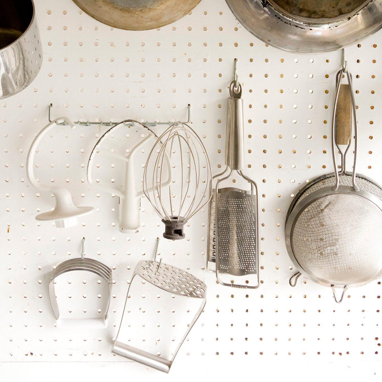 Cooking utensils hanging on white peg board