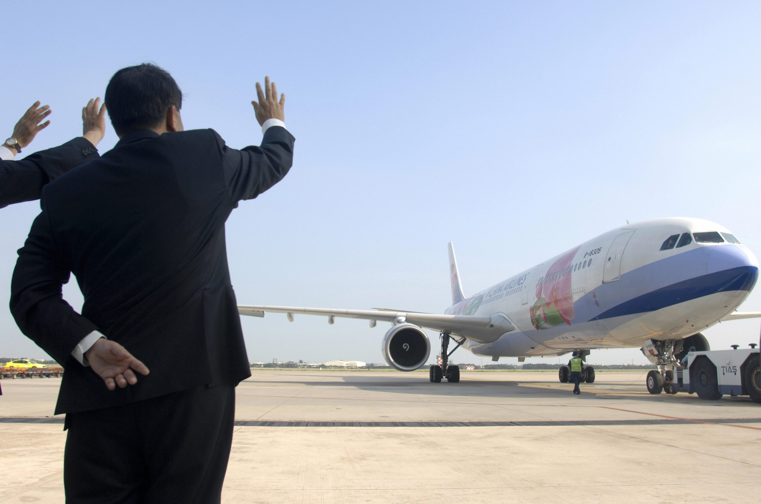 China Airlines officials wave before a f
