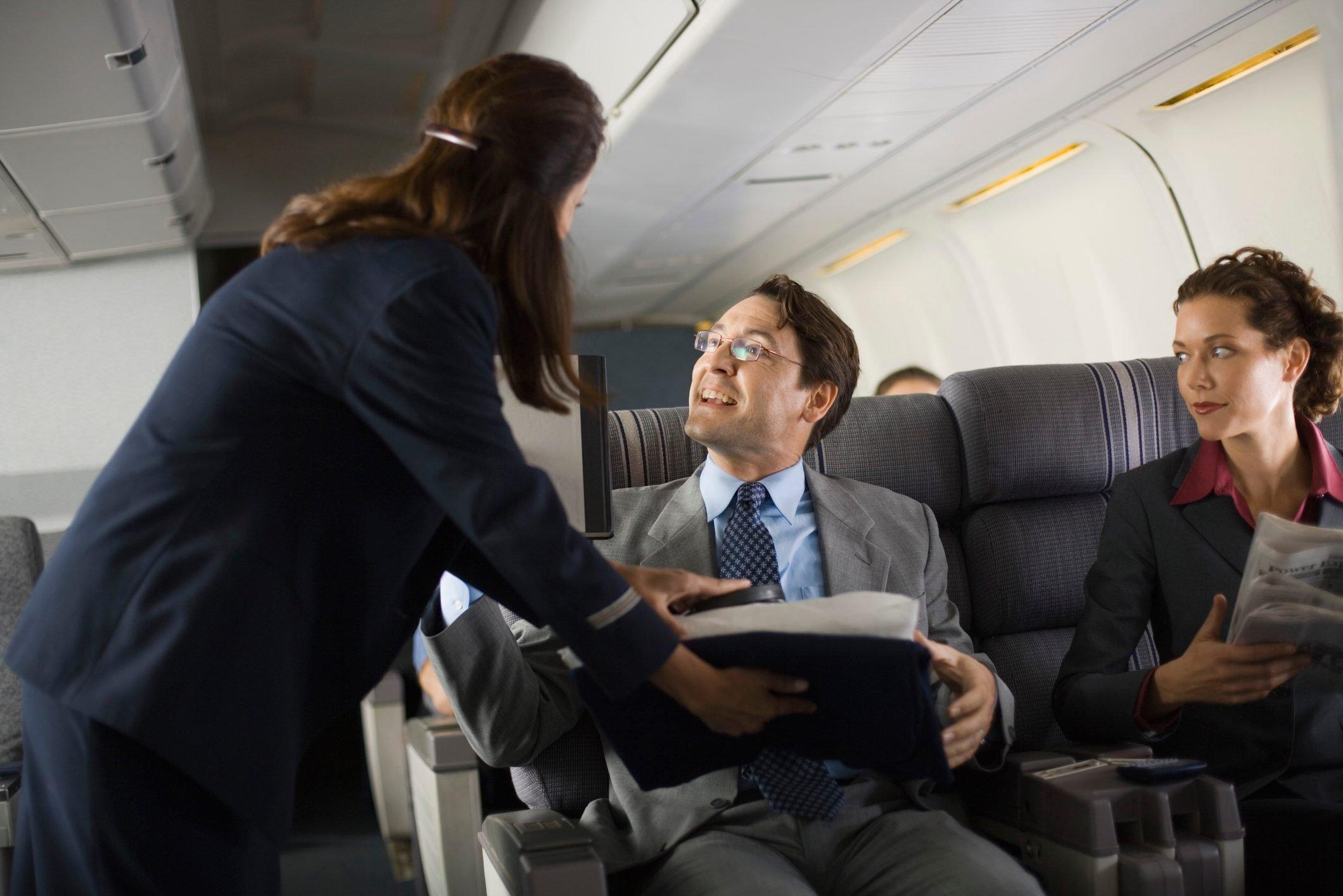 Stewardess handing blanket and pillow to passenger