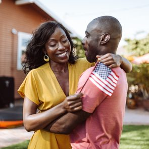 Couple embracing holding American flag
