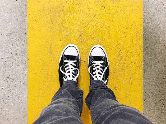 Low Section Of Man Standing On Yellow Concrete Footpath