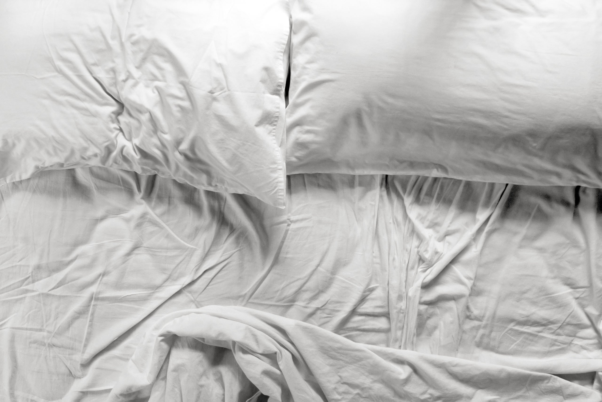 Unmade bed in a bedroom with two pillows and crumpled bed sheet