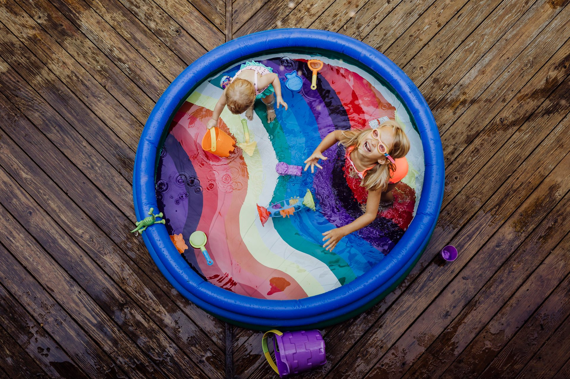 High angle view of sisters playing in wading pool on wood