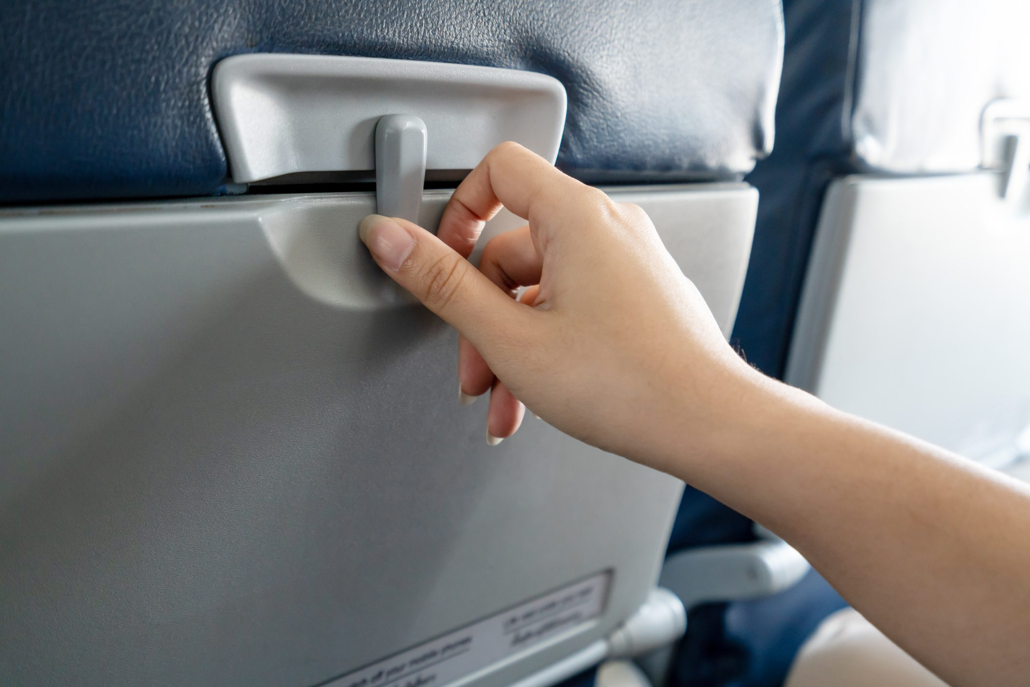 Hand of asian female passenger try to open a tray in front of the seat in low cost airplane by slide to unlock and ready for inflight meal or food service. Plastic table in back seat in economy class.