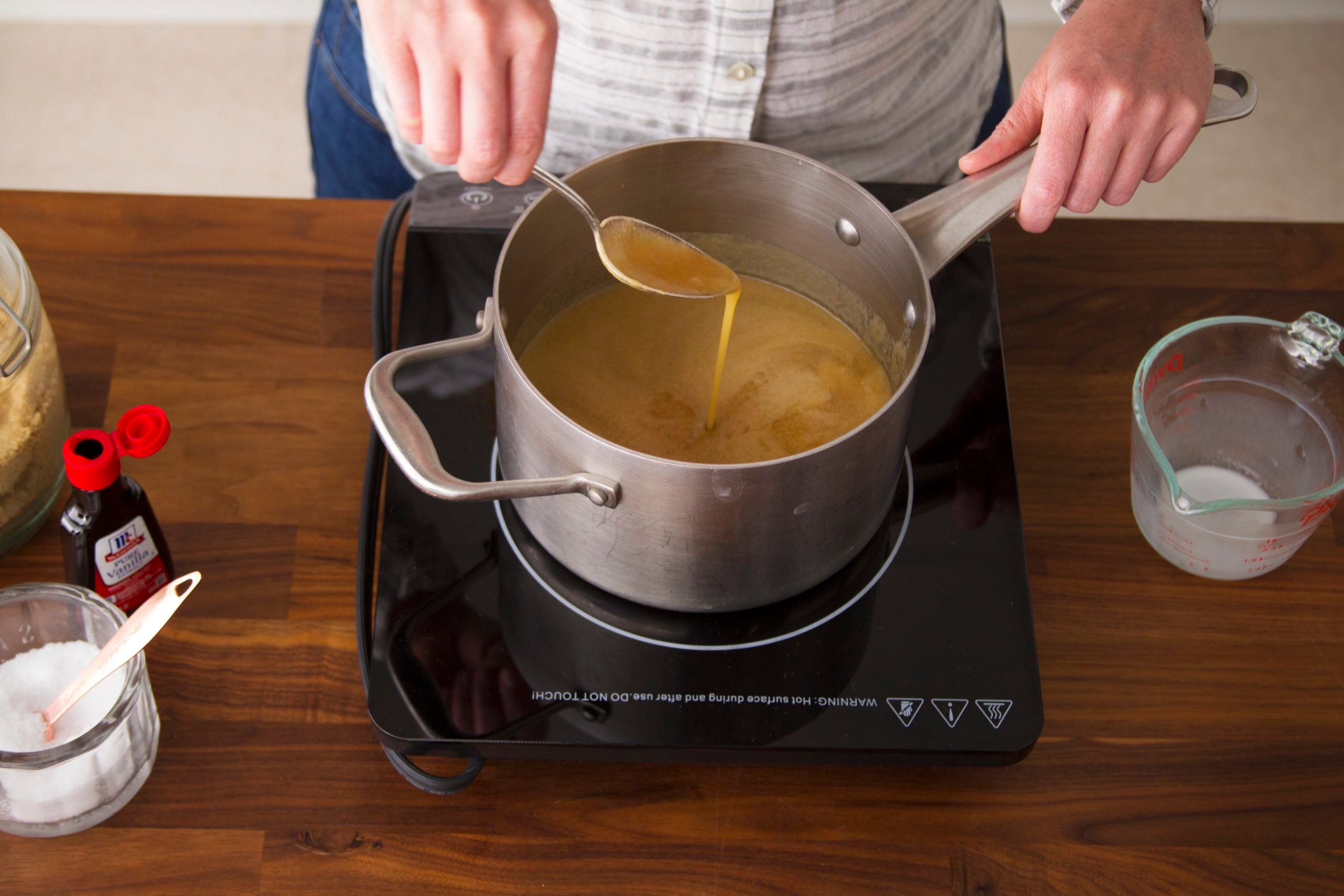 Person stirring melted butter in a saucepan on the stovetop