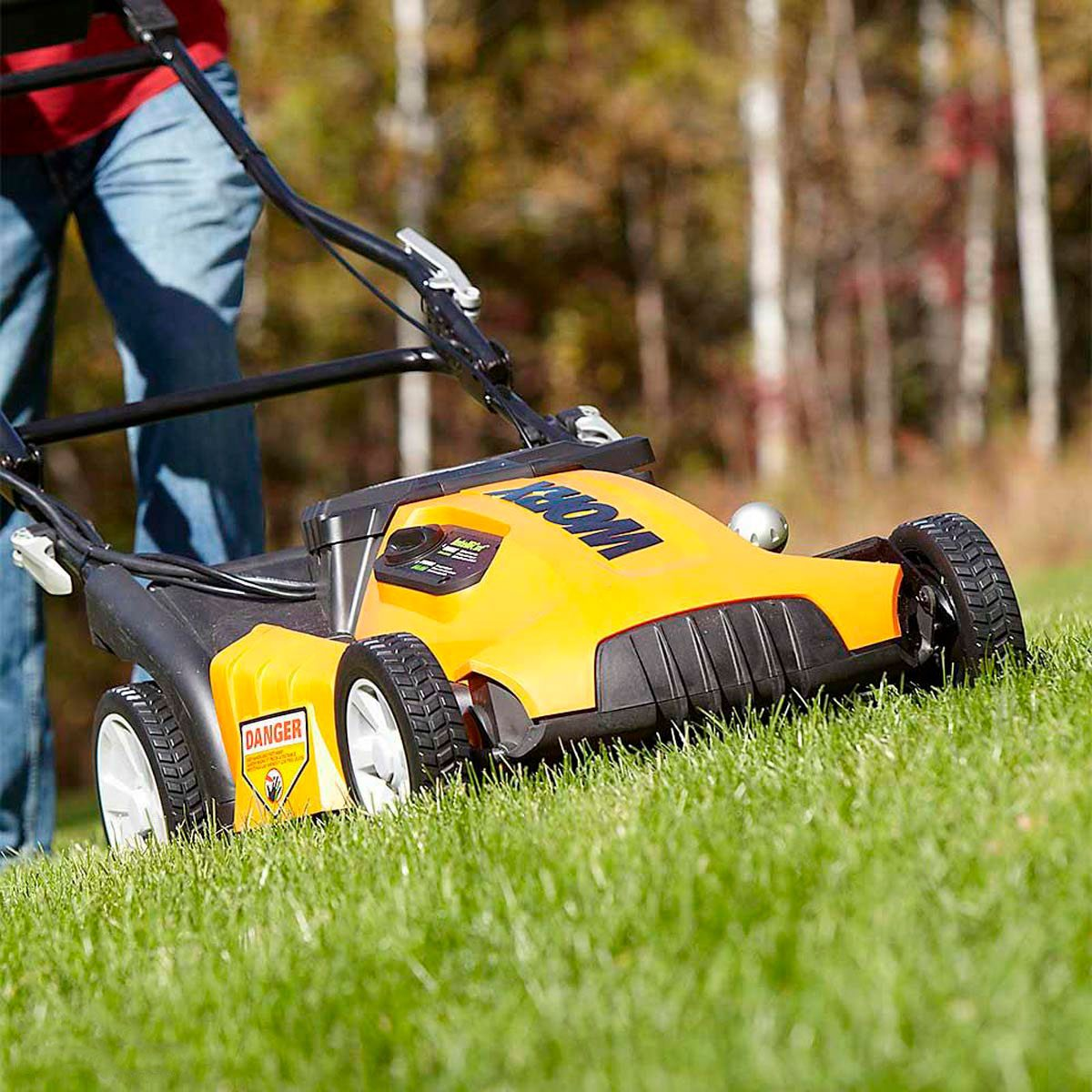 mowing the lawn. yellow push lawnmower.
