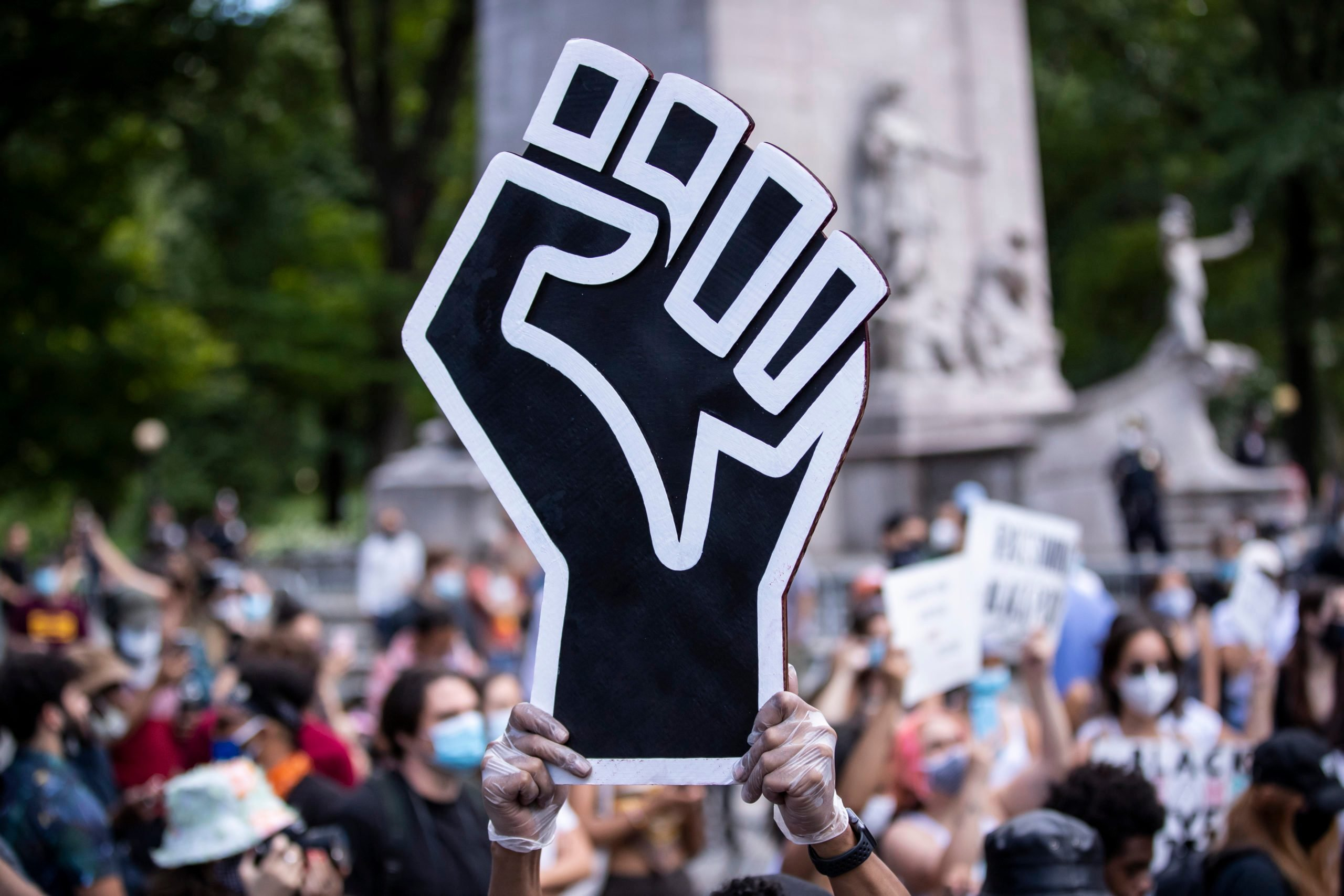 A protestor holds up a large black power fist in the middle of a crowd gathered at Columbus Circle in New York City for a George Floyd Black Lives Matter Protest