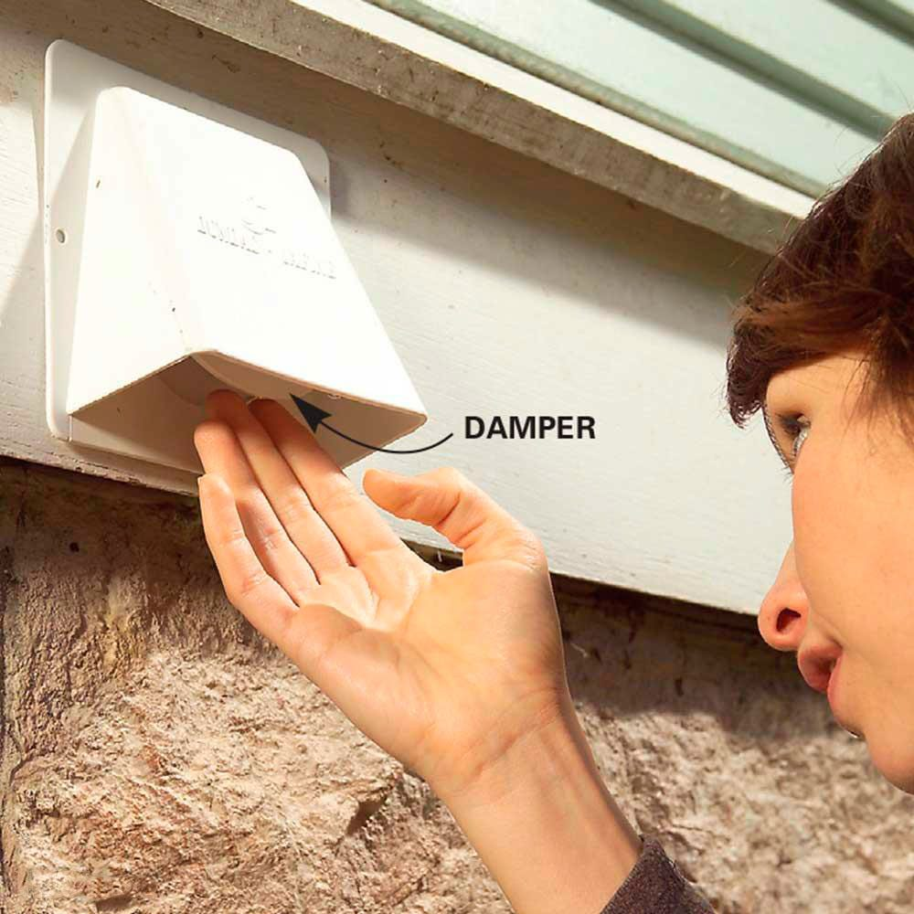 woman checks dryer vent