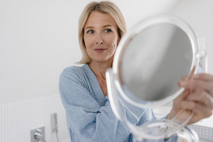 Mature woman looking in beauty mirror in bathroom