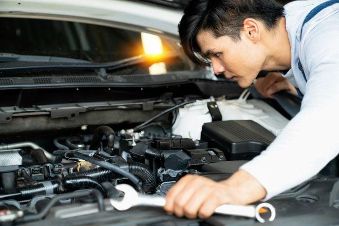 Mechanic fixing car engine in auto repair shop.Auto mechanic working in garage. Repair service.