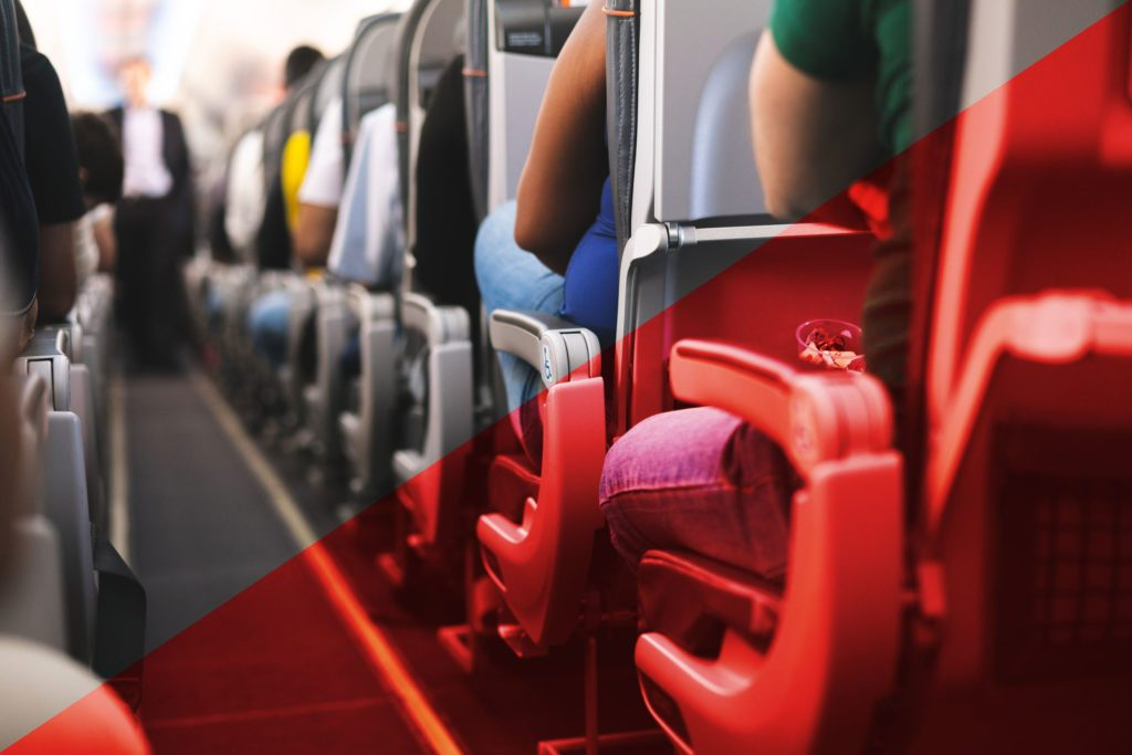 view down the aisle of a crowded plane with red overlay on one half