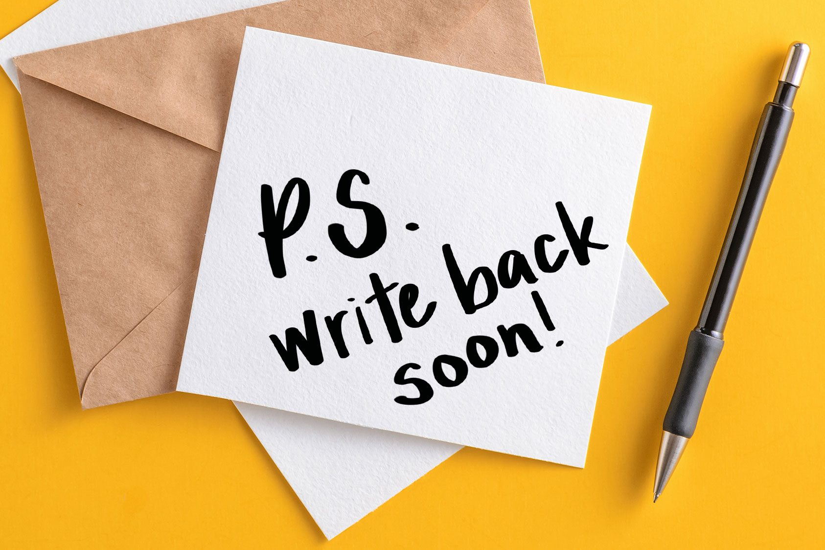 """""""P.S. write back soon"""" written on stationary; yellow background"""