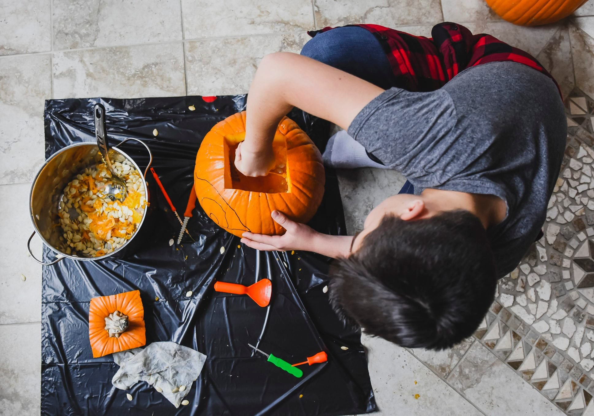 High angle view of boy removing seeds from pumpkin at home
