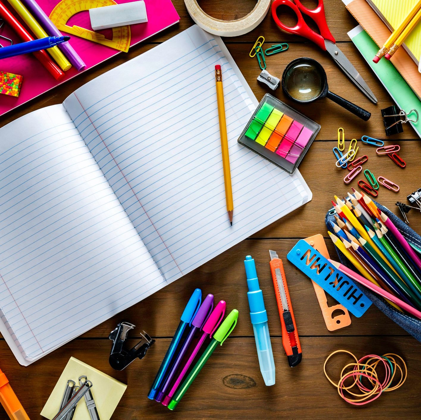 Overhead shot of stationery on wood desk with paper notepad and frame of school office supplies