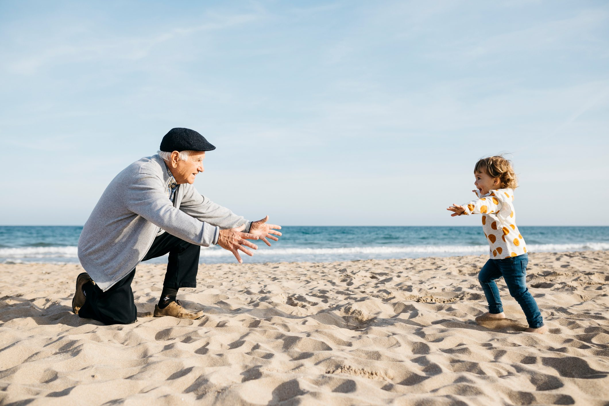 Grandfather playing with his granddaughter on the beach