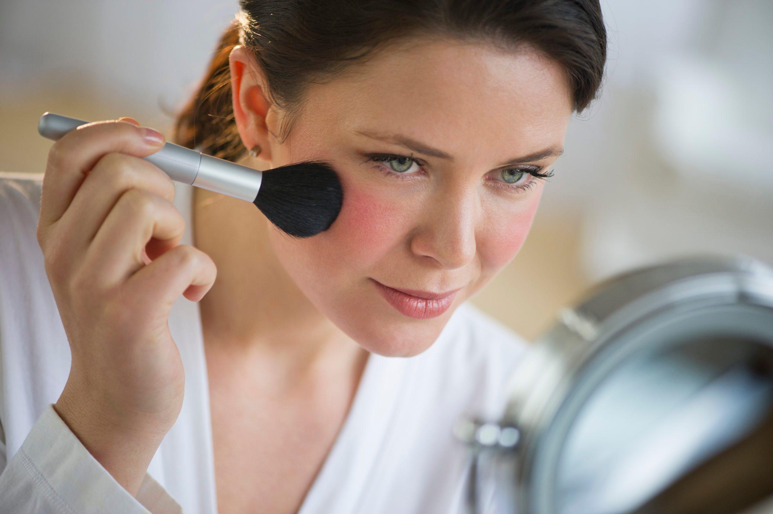 USA, New Jersey, Jersey City, woman applying blush on cheekbones