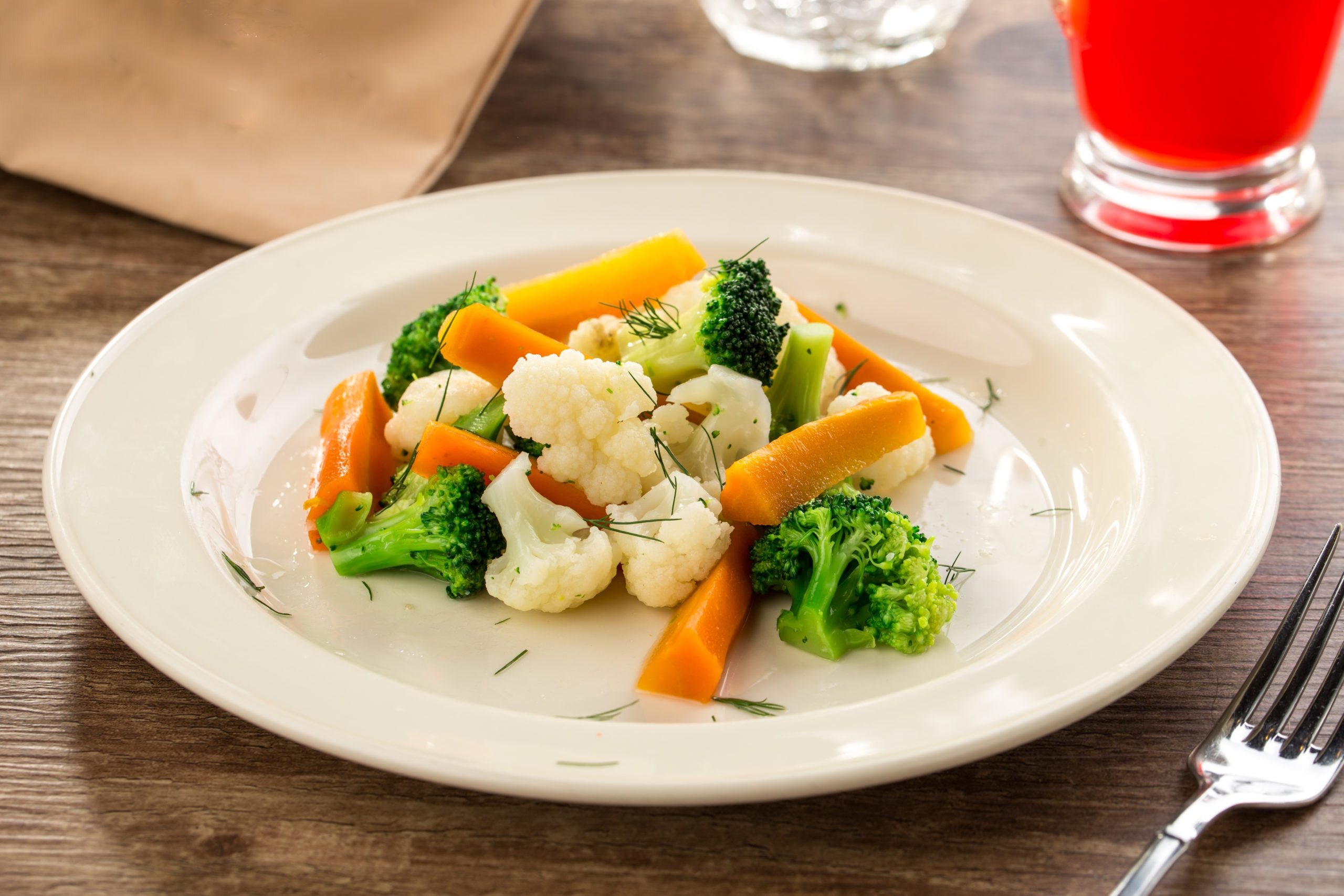 Mixed vegetables cauliflower, broccoli and carrots on white plate on wooden background