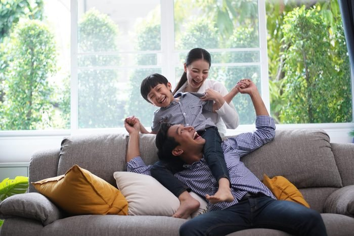 Family playing together father giving his son piggyback ride happiness time together at home