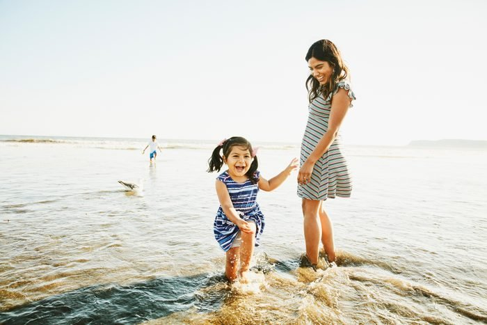 Laughing young girl playing in surf with mother and brother