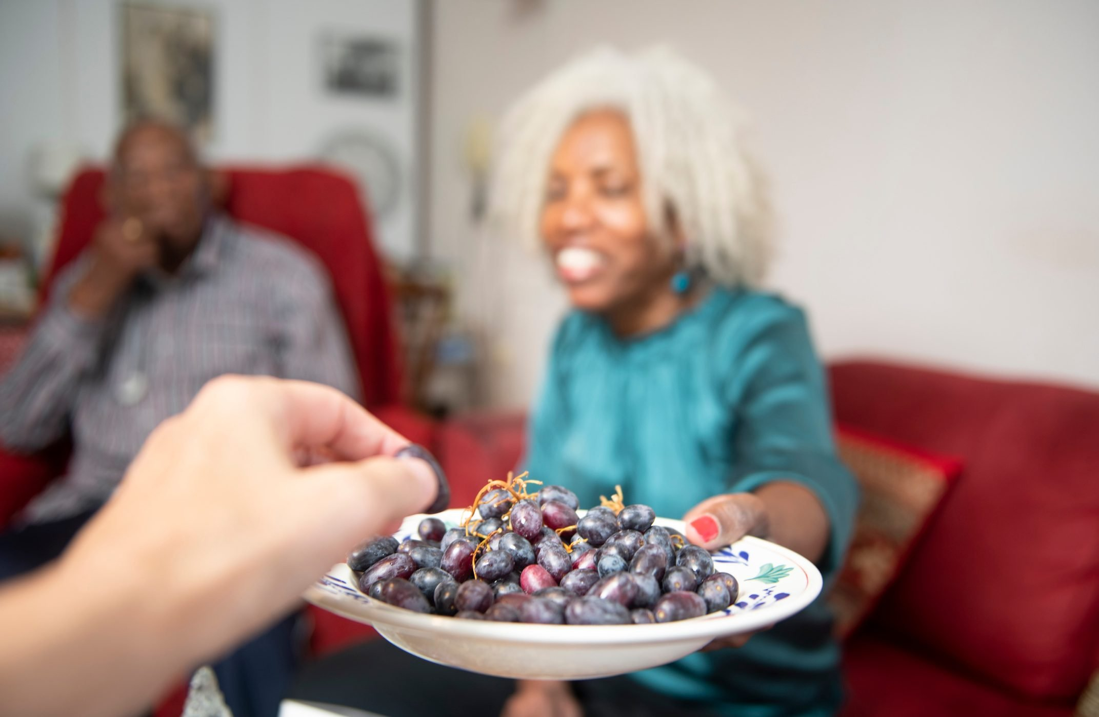 Personal view of a guest being offered grapes by a kind and beautiful senior woman