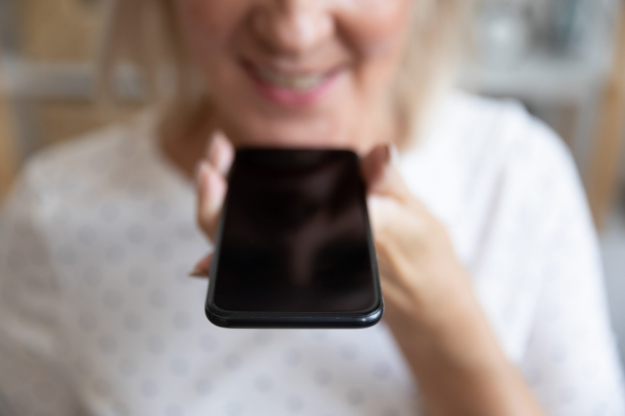Close up mature woman holding phone, recording voice message