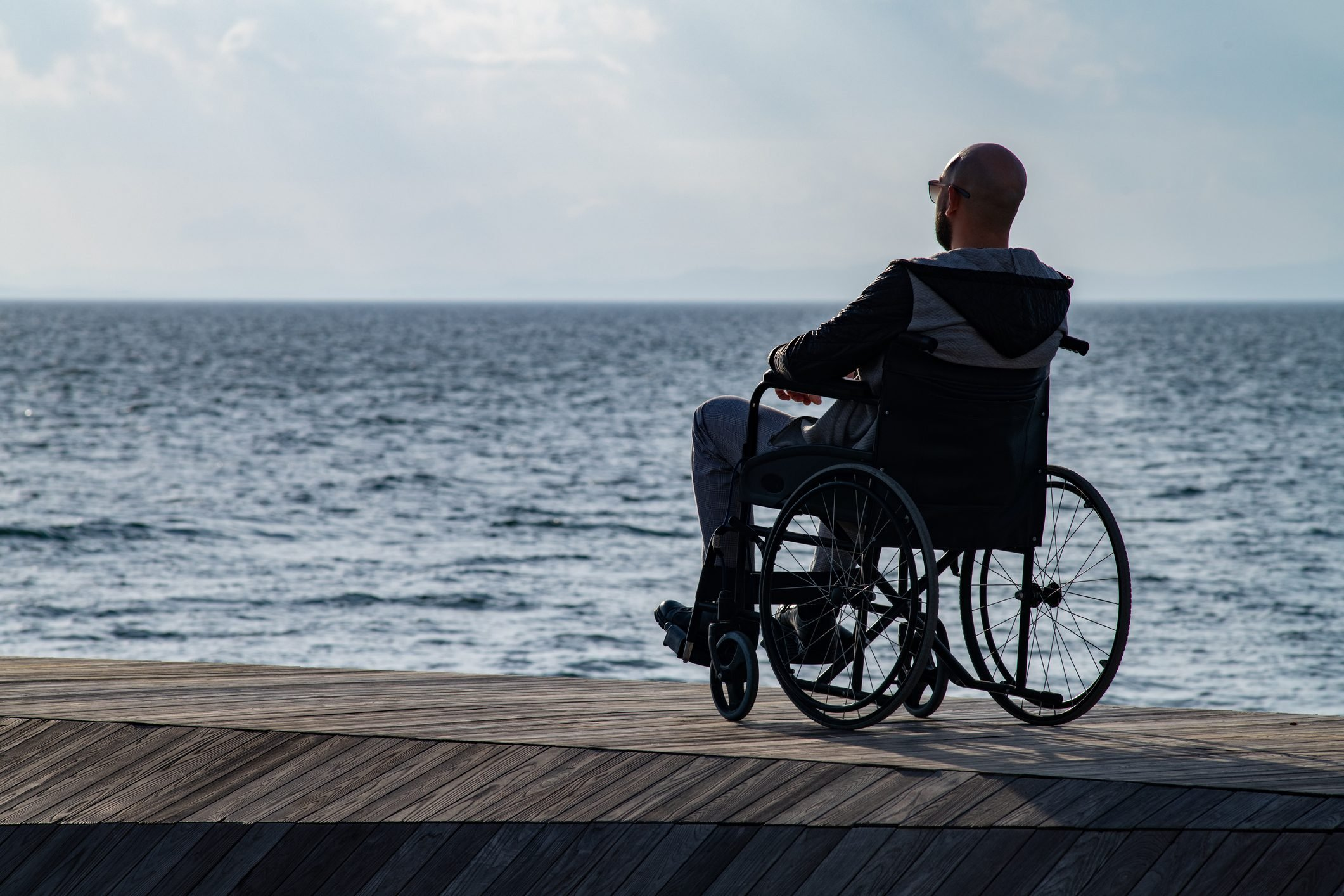 rear view of man in wheelchair at the beach