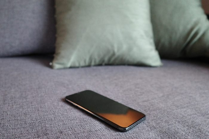 Close-Up Of Smart Phone On Sofa