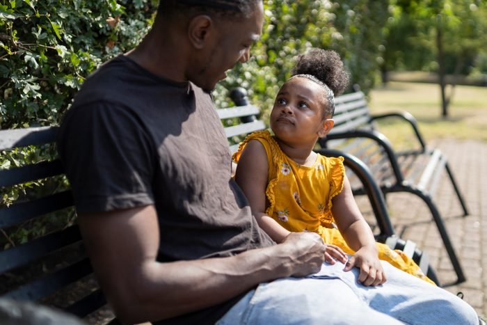 Father and daughter sitting on a bench in a park