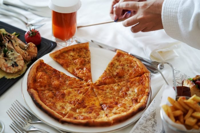 Pizza slices, Shrimp in sauce and french fries on a white table close-up