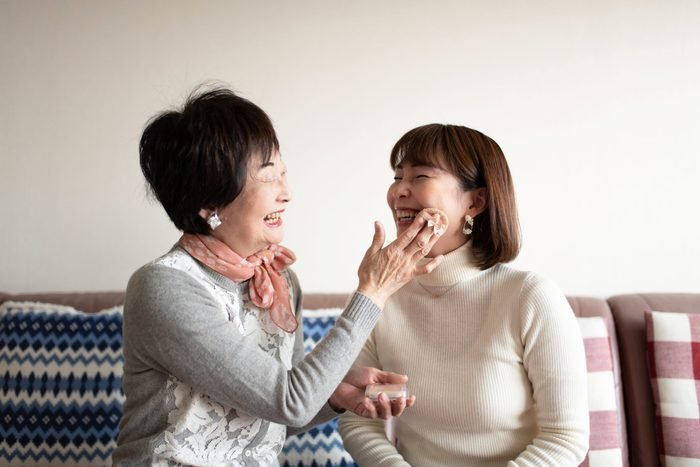 Senior woman making up at home with mid adult woman