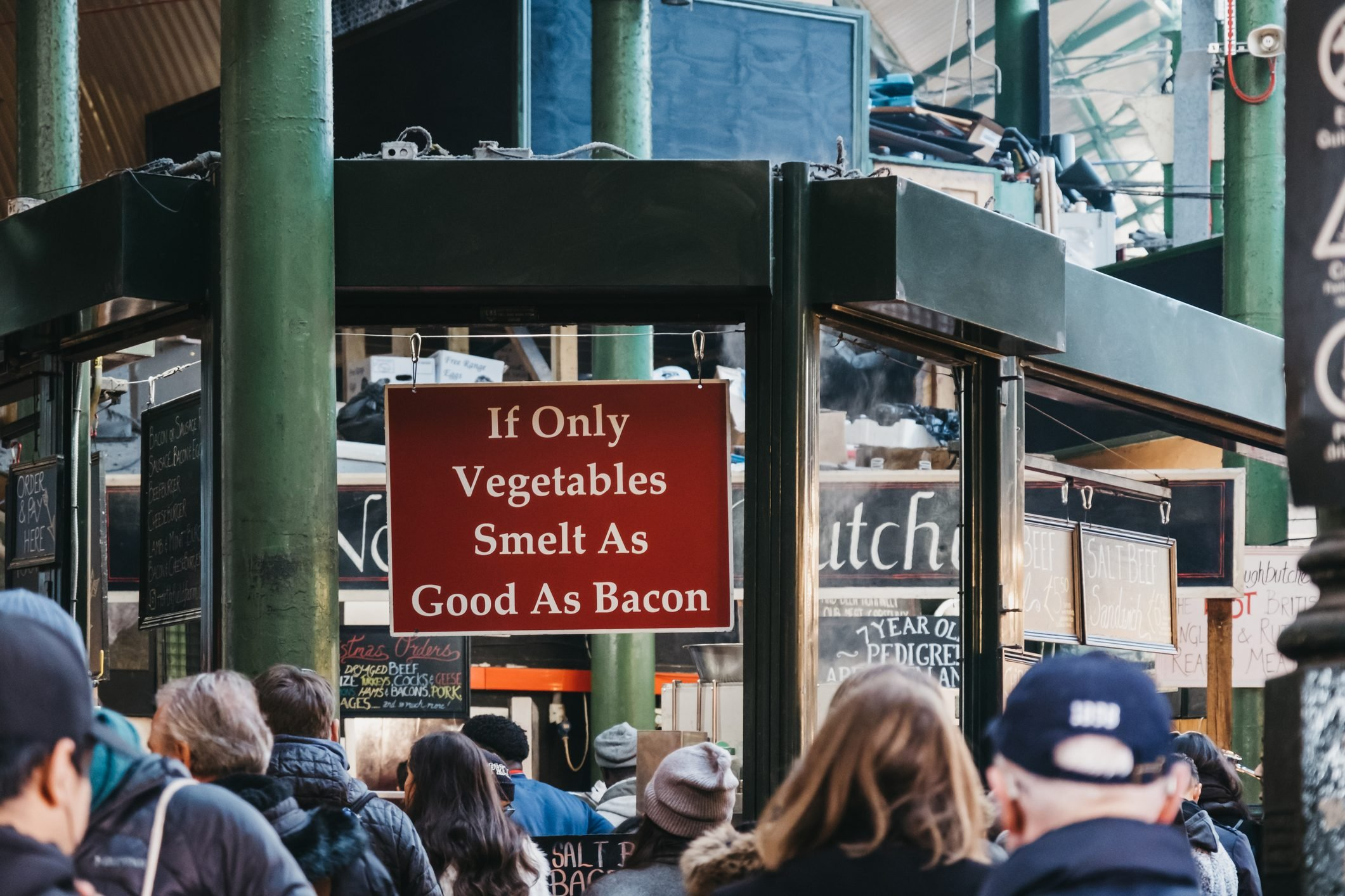 """""""If only vegetables smelt as good as bacon"""" sign at Northfield butchery stall in Borough Market, London, UK."""