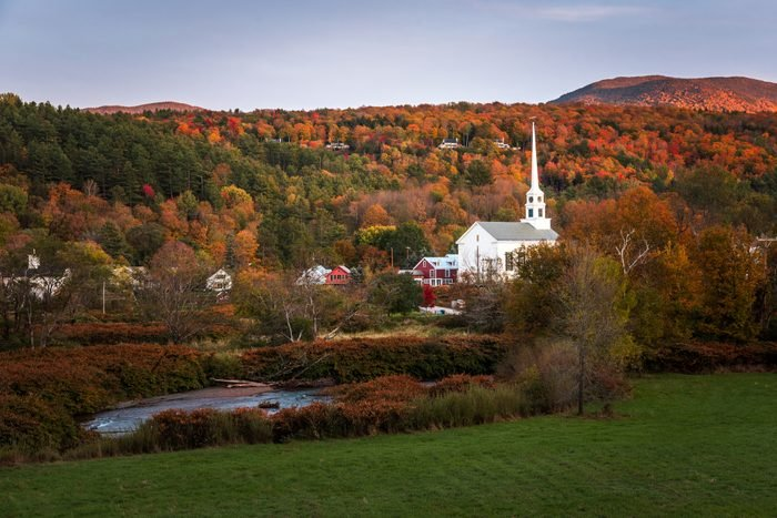 Traditional white wooden church in a town surrounded by mountains covered in colourful autumnal trees at sunset