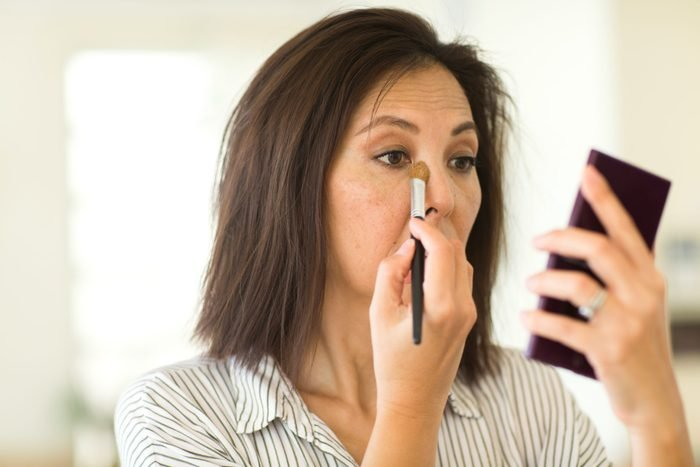 Asian woman applying make up.