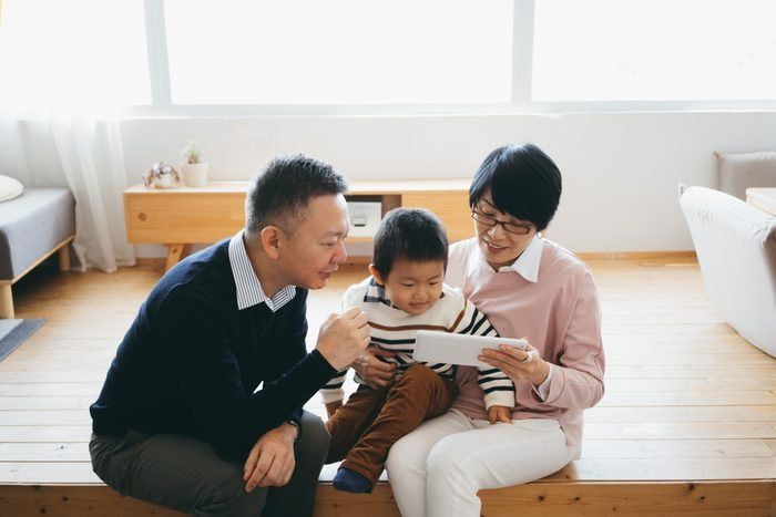 Joyful Asian grandparents sitting on the floor in the living room using digital tablet with little grandson together at home