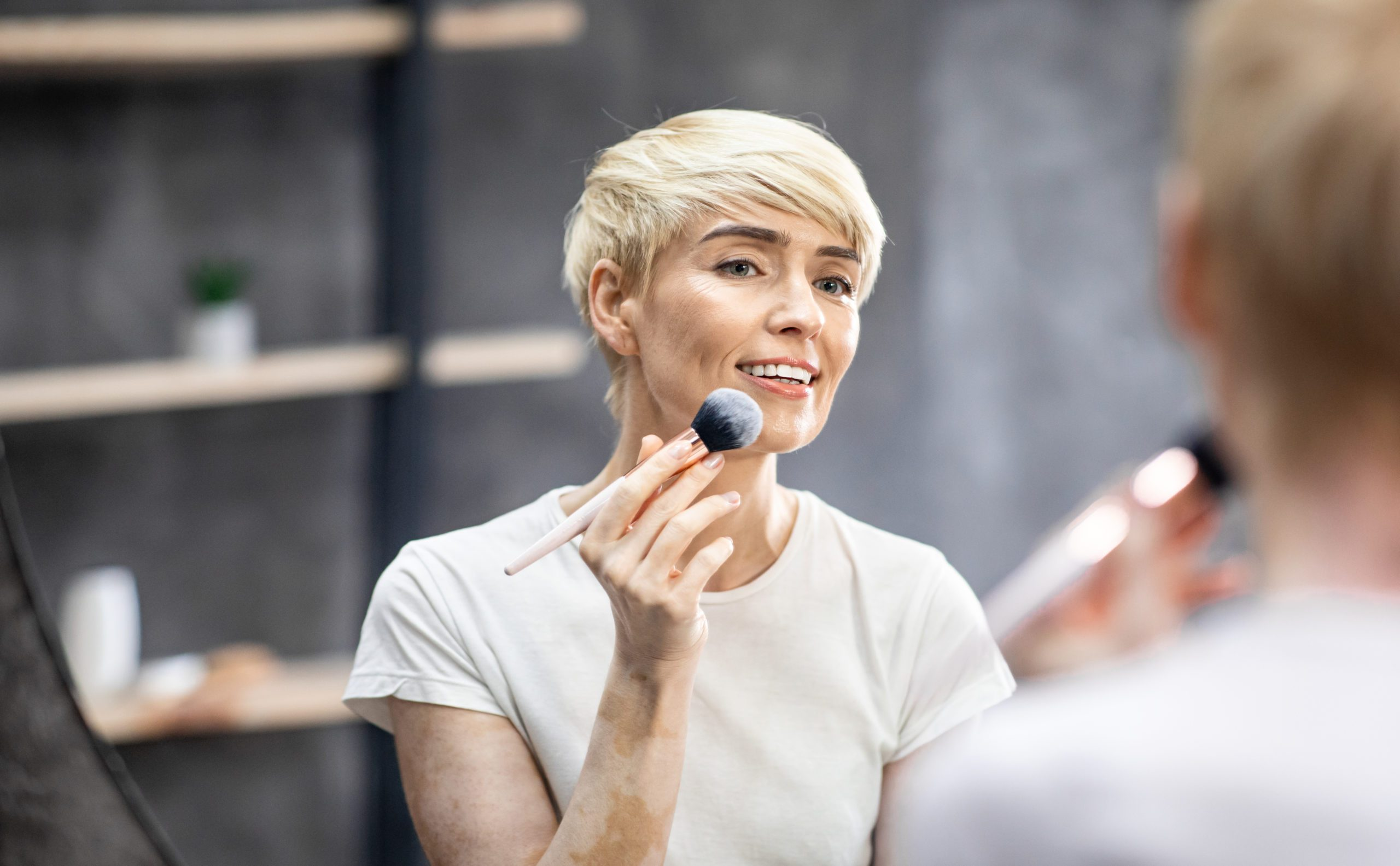 Middle-Aged Lady Using Makeup Brush Applying Bronzer Standing At Home