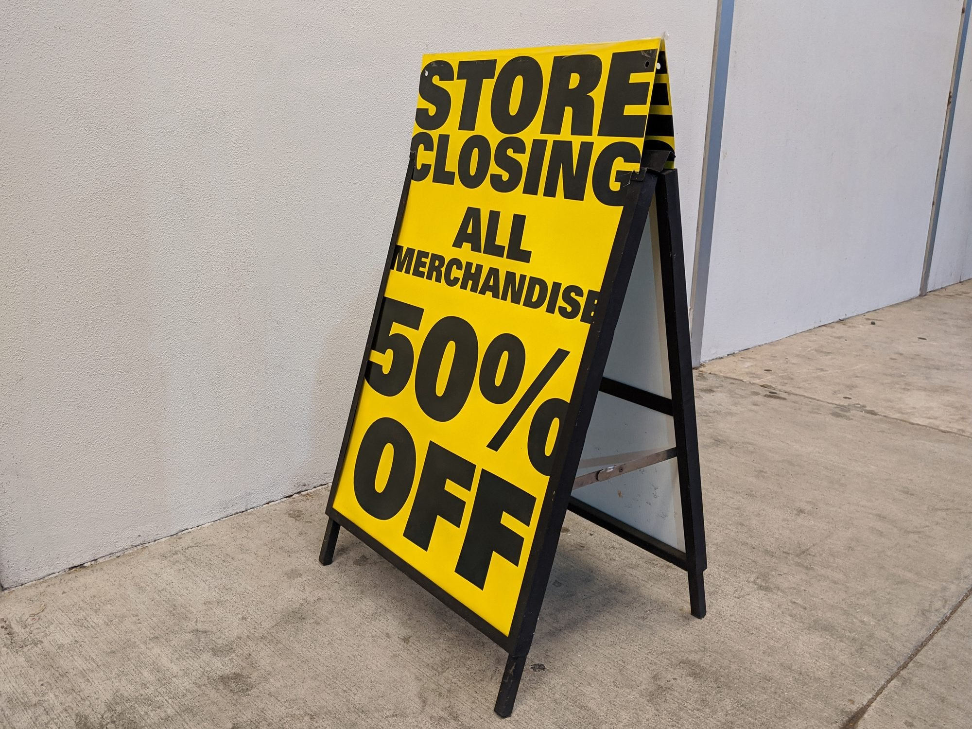Store Closing 50% Off sign outside of a liquidated business