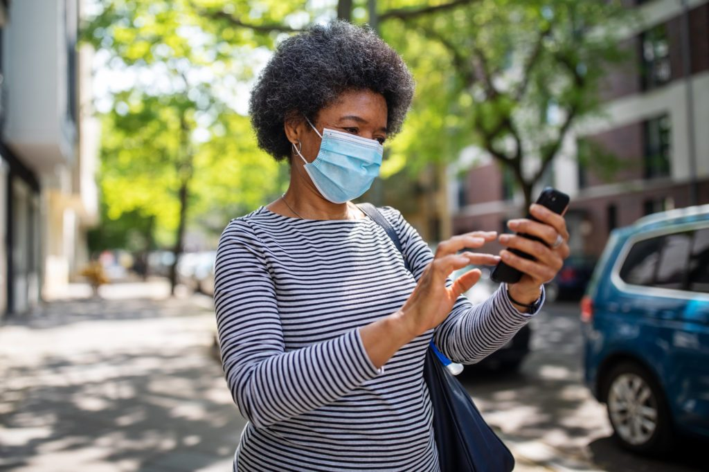 Woman walking on the street during corona virus outbreak using phone