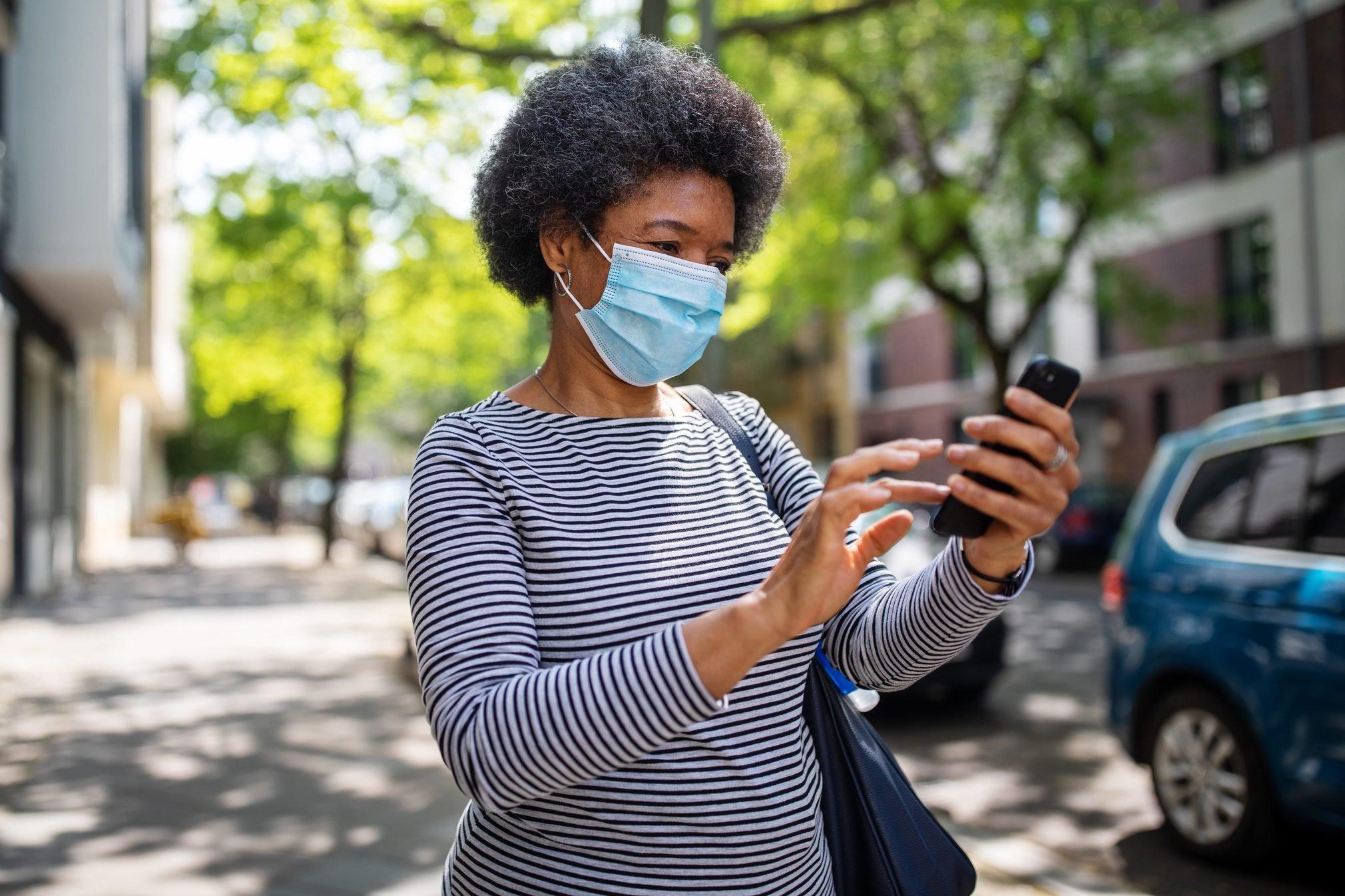 Woman walking on the street during corona virus outbreak using phone