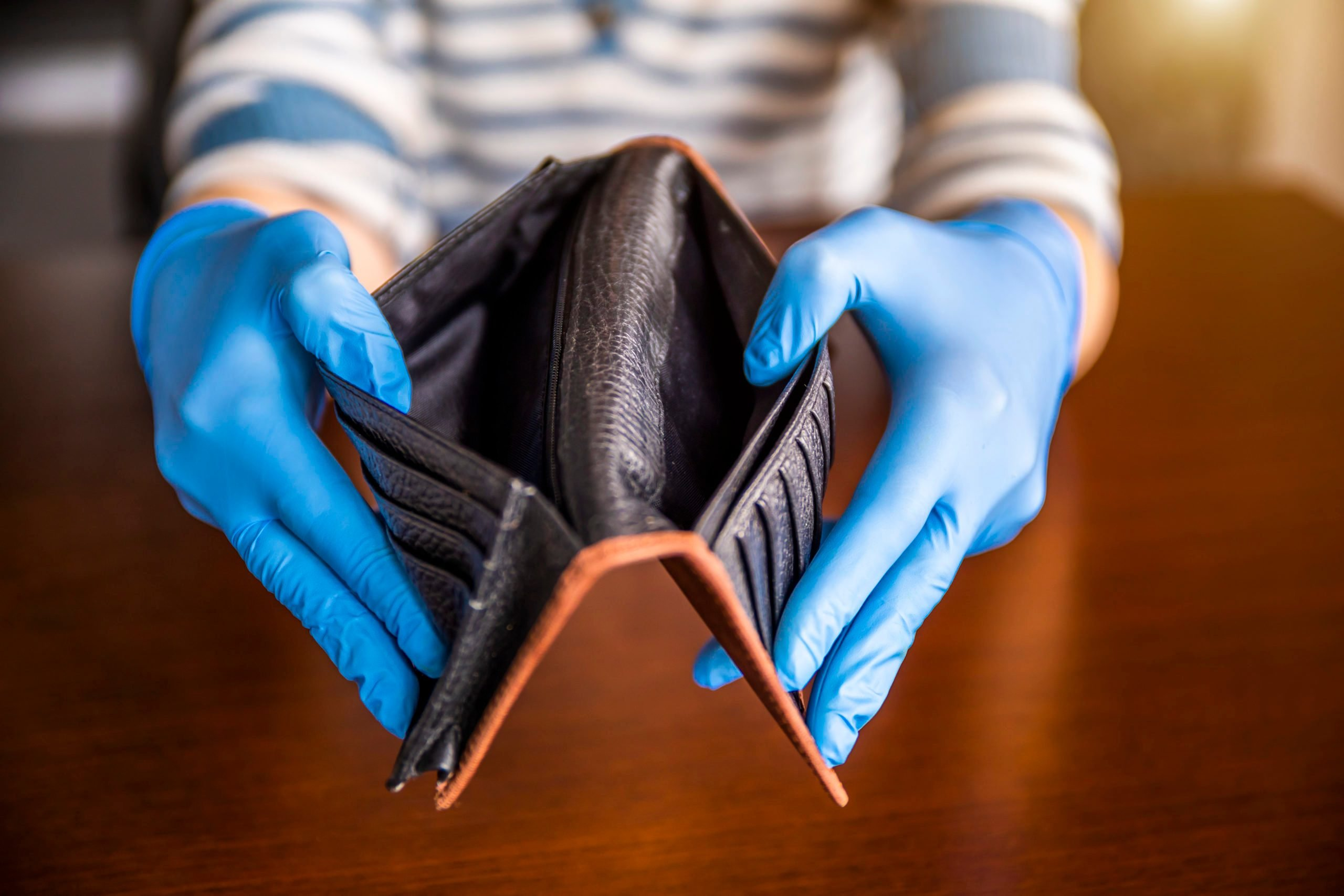 Person wearing medical protective gloves holding empty wallet, economic crisis