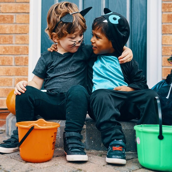 Two children dressed for Halloween with their arms around each others shoulders.