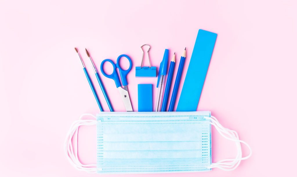 Back to school concept, pencil case, stationery and school supplies and medical face masks. Top view, copy space, pink background. Protection against coronavirus of schoolchildren and students. Studying in the new reality pandemic.