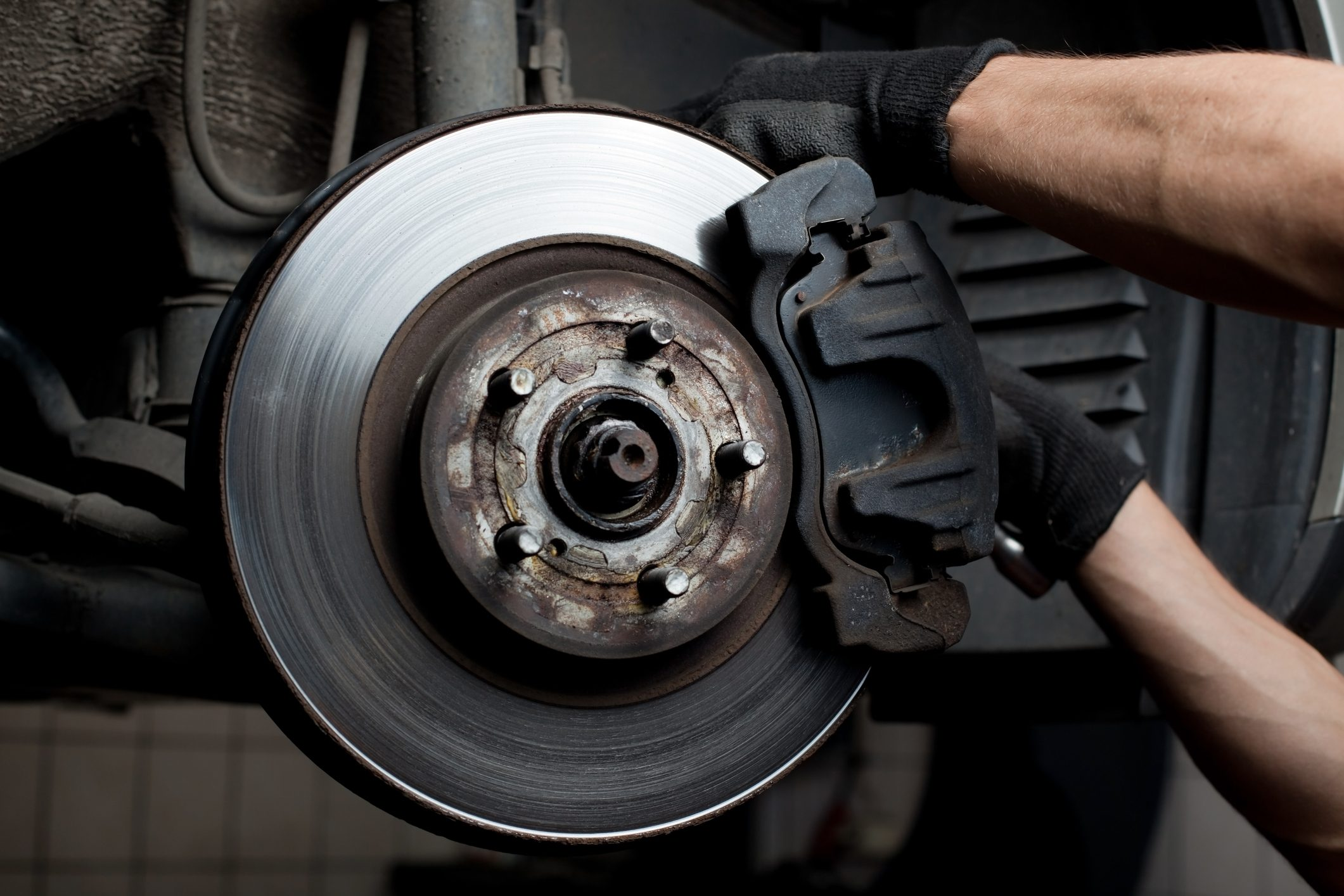 A mechanic working on a brake pad
