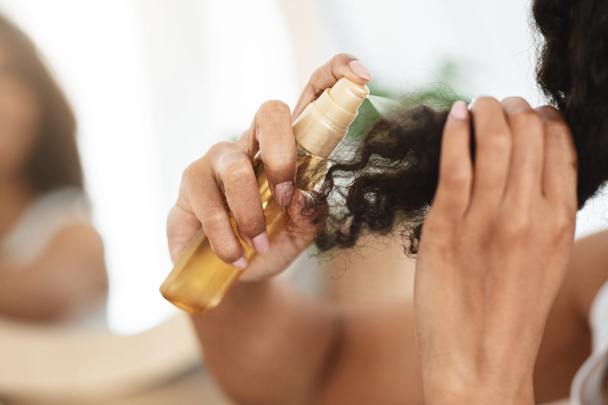 Split Ends Remedy. Unrecognizable Black Woman Applying Moisturising Spray To Curly Hair