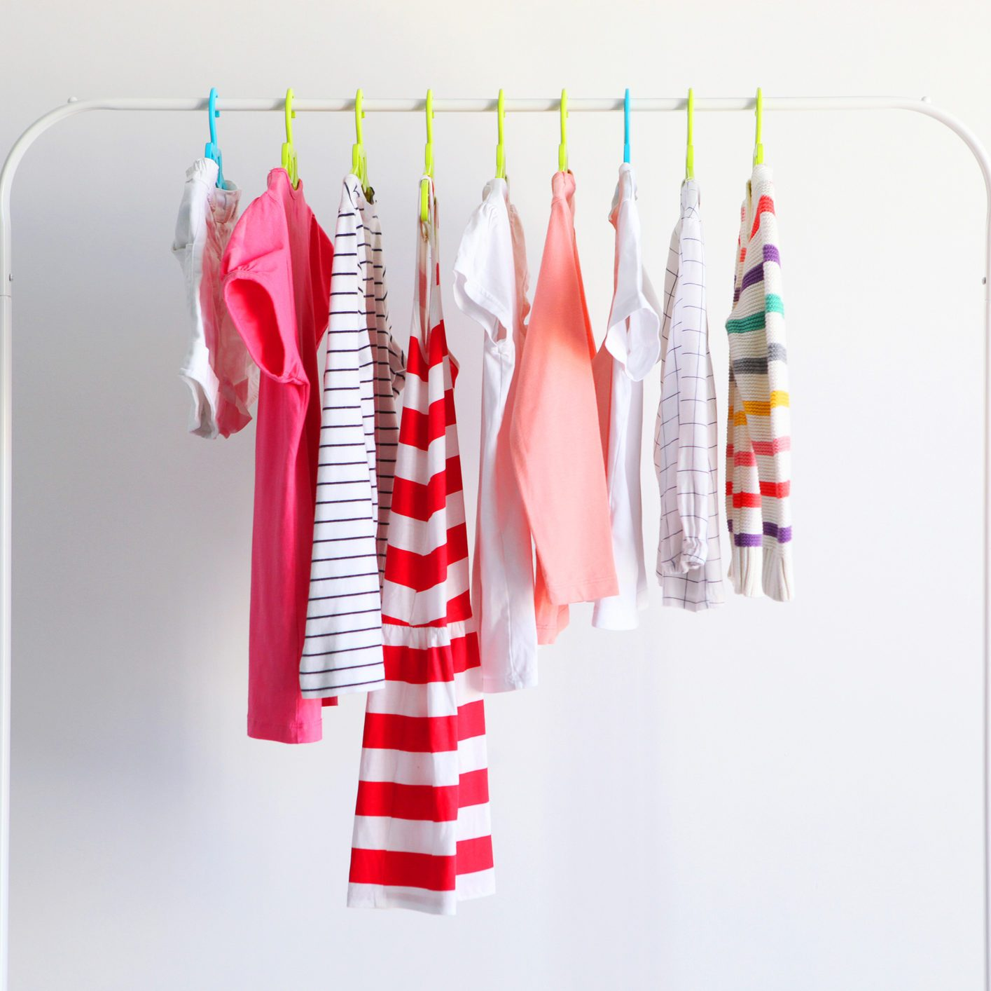 Children clothes on a rack on a light background. Children's clothing, children's stores.
