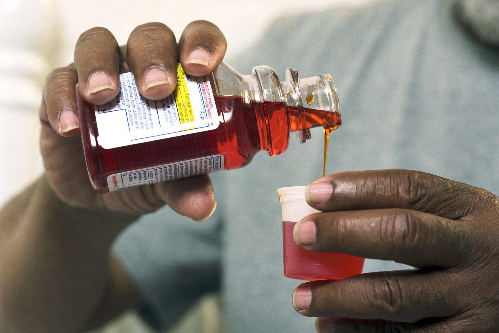 Senior man pouring medicine out of bottle, close-up