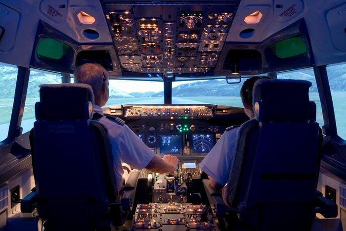 Pilots sitting in flight simulator, rear view